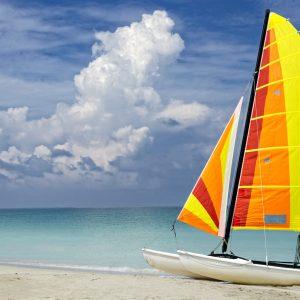 A catamaran is left unused on a Caribbean beach as a storm approaches.